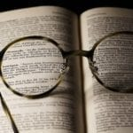 Okulary leżą na książce i pozwalają zauważyć tekst, zupełnie jak algorytm Boyera-Moore-a
