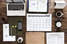 Biurko z przyrządami do organizacji czasu takimi jak laptop, telefon, notes, notatnik i kalendarz