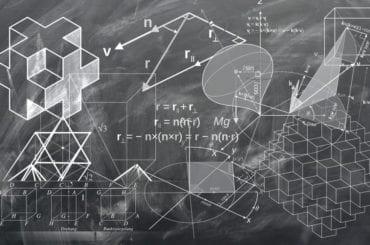 Zapiski matematyczne narysowane na czarnej tablicy białą kredą szkolną