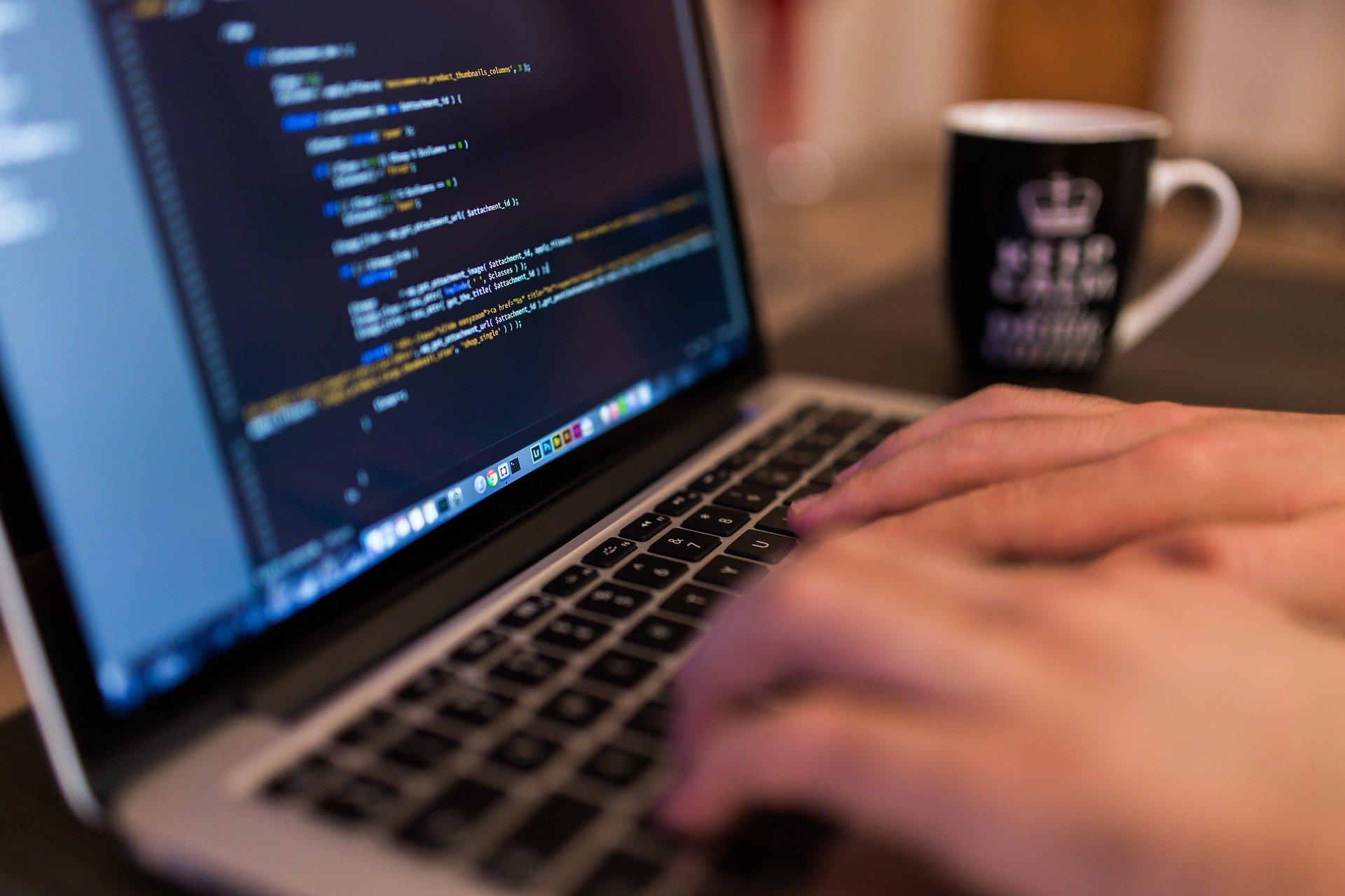 Zdjęcie pracującego przed komputerem mężczyzny, który programuje